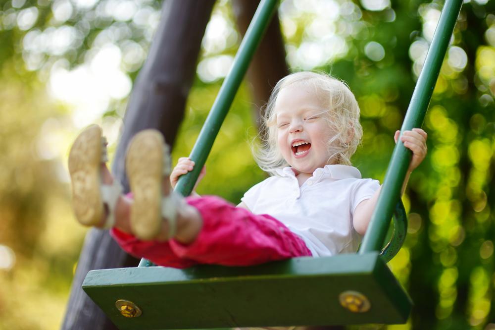 kleines Mädchen hat Spass auf einer Gartenschaukel
